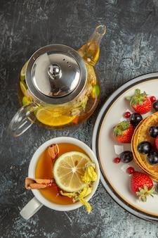 Vista superior deliciosas panquecas com frutas e chá em uma mesa leve com frutas doces no café da manhã