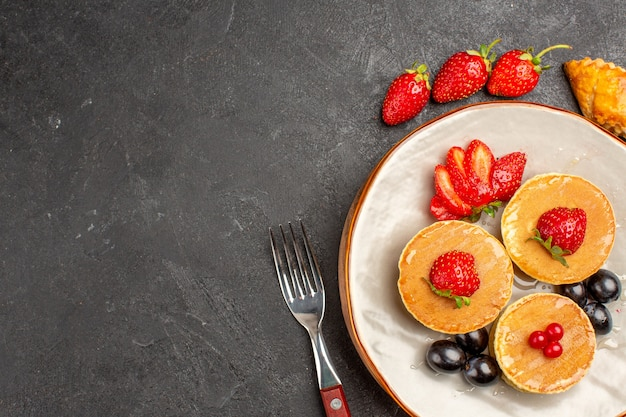 Vista superior deliciosas panquecas com frutas em piso escuro torta bolo de frutas doce
