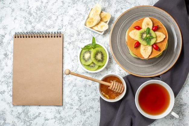 Vista superior deliciosas panquecas com frutas fatiadas e xícara de chá na superfície branca frutas doce sobremesa açúcar bolo de café da manhã