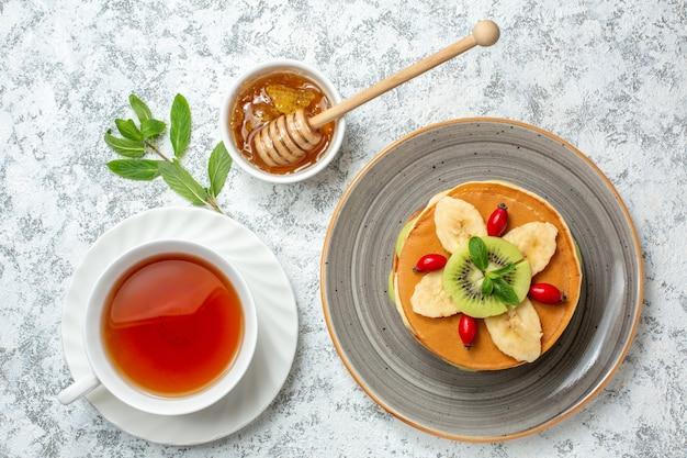 Vista superior deliciosas panquecas com frutas fatiadas e xícara de chá na superfície branca frutas doce sobremesa açúcar café da manhã cor bolo