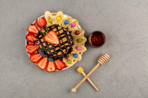 Vista superior deliciosas panquecas com frutas frescas e chocolate no chão cinza