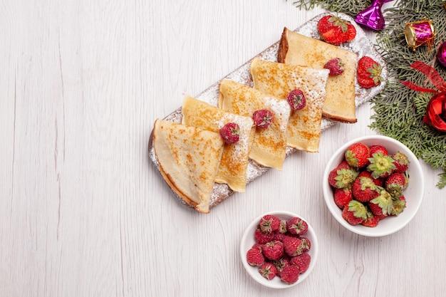Vista superior deliciosas panquecas com frutas no fundo branco doce bolo sobremesa frutas chá panqueca