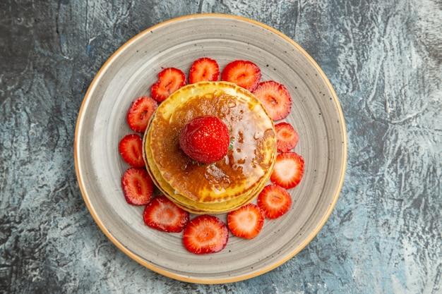Vista superior deliciosas panquecas com mel e morangos na luz