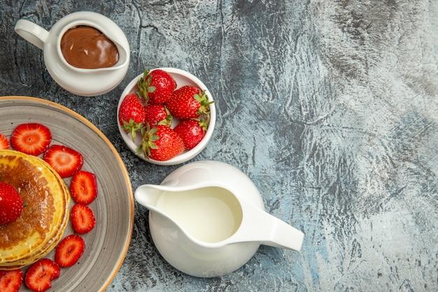 Vista superior deliciosas panquecas com morangos e mel na luz