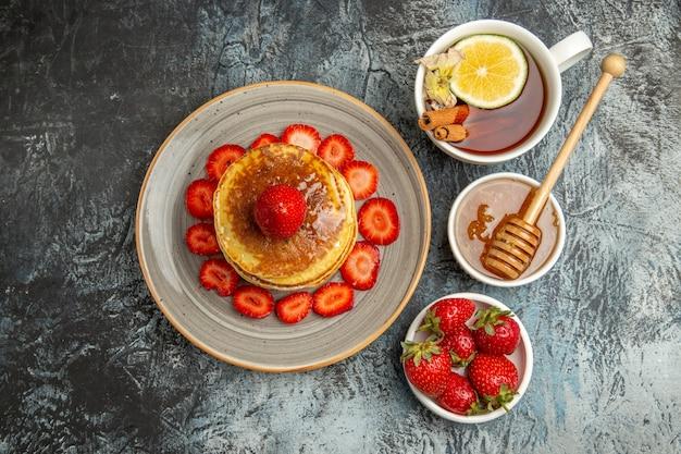Vista superior deliciosas panquecas com morangos e xícara de chá na luz