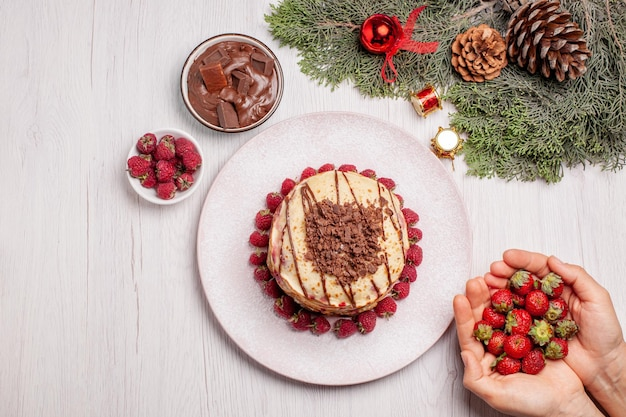 Vista superior deliciosas panquecas com morangos em uma mesa branca torta de frutas vermelhas bolo doce biscoito