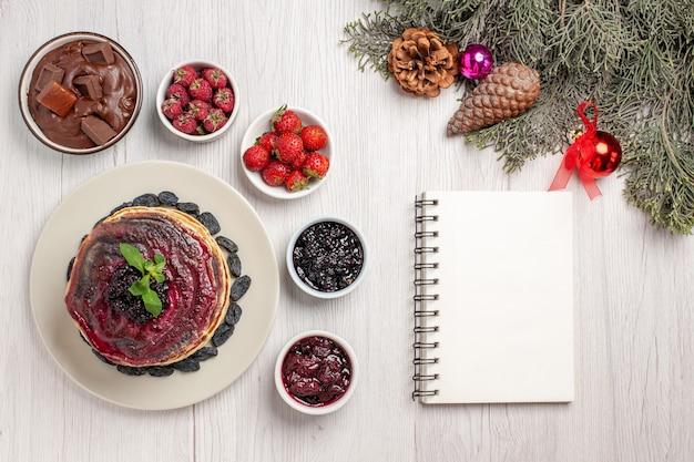 Vista superior deliciosas panquecas de gelatina com frutas e geléias em branco