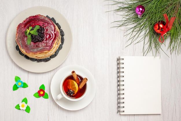 Vista superior deliciosas panquecas de gelatina com passas, geléia de frutas e xícara de chá no fundo branco, bolo de geleia, biscoito, sobremesa, doce