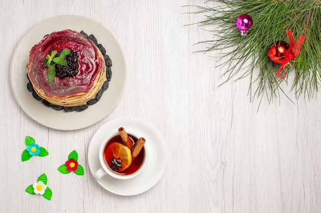 Vista superior deliciosas panquecas de geléia com passas, geléia de frutas e uma xícara de chá no fundo branco claro, bolo de geléia, biscoito, sobremesa doce
