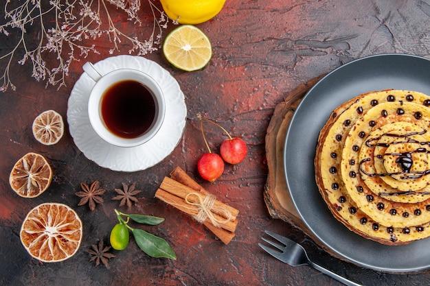 Vista superior deliciosas panquecas doces com chá na superfície escura