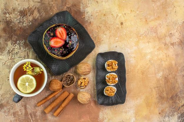 Vista superior deliciosas panquecas doces com uma xícara de chá na mesa de madeira