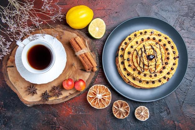 Vista superior deliciosas panquecas doces com uma xícara de chá na superfície escura