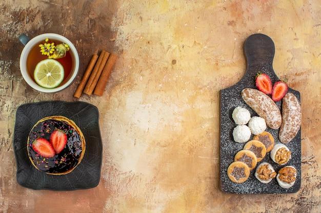Vista superior deliciosas panquecas doces com xícara de chá e doces na mesa leve