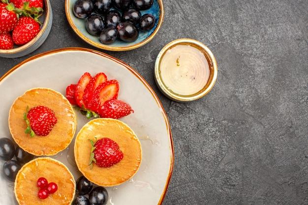 Vista superior deliciosas panquecas pouco formadas com frutas no cinza