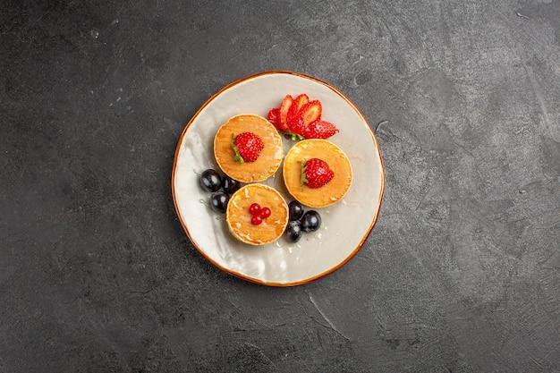 Vista superior deliciosas panquecas pouco formadas com frutas no escuro
