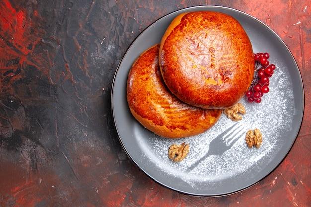 Vista superior deliciosas tortas com frutas vermelhas em uma mesa escura tortas de bolo doce