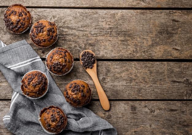 Vista superior delicioso arranjo de muffins em fundo de madeira