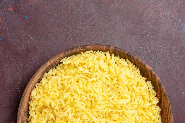 Vista superior delicioso arroz cozido dentro de um prato marrom na mesa escura
