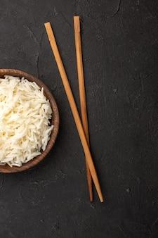 Vista superior delicioso arroz cozido simples arroz saboroso dentro de um prato marrom no espaço escuro