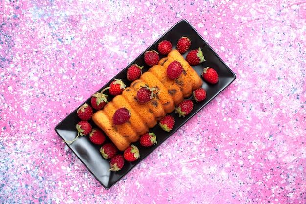 Vista superior delicioso bolo assado dentro da fôrma preta com morangos vermelhos frescos na mesa rosa.