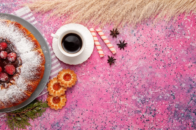 Vista superior delicioso bolo de morango com açúcar em pó com biscoitos e chá no fundo rosa claro bolo biscoito doce chá de biscoito