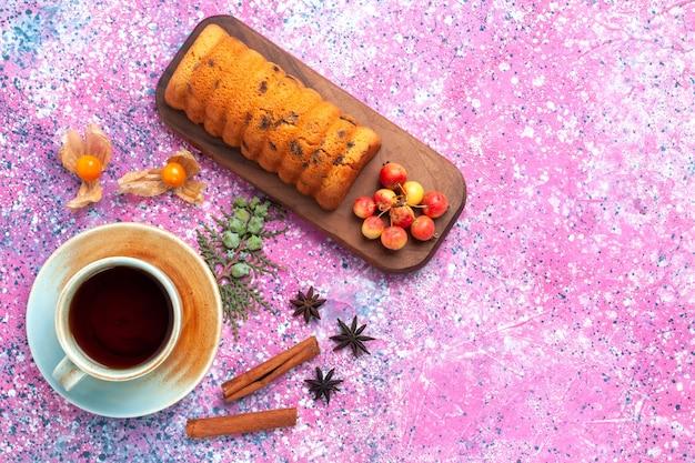 Vista superior delicioso bolo doce e gostoso com uma xícara de chá de cerejas na mesa rosa.