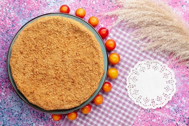 Vista superior delicioso bolo redondo dentro do prato com ameixas de cereja alinhadas na mesa rosa brilhante torta de bolo biscoito doce assar frutas