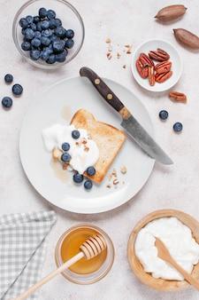 Vista superior delicioso café da manhã com torradas e mel