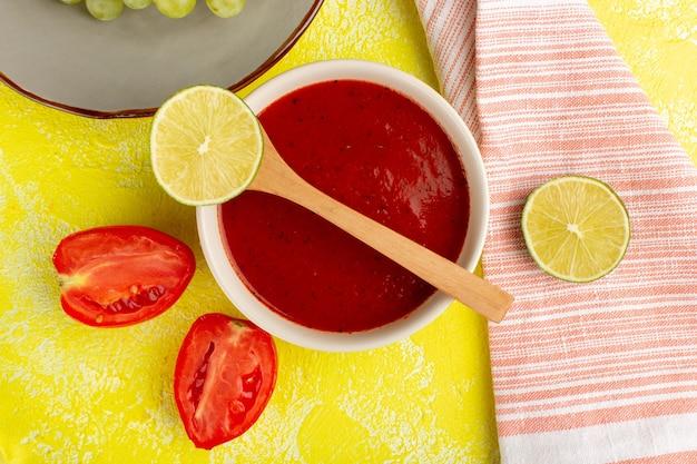 Vista superior delicioso molho de tomate com limão e tomate na mesa amarela sopa comida refeição jantar