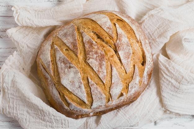 Vista superior delicioso pão assado no pano branco