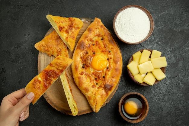 Vista superior - delicioso pão com ovo assado em fatias em um espaço cinza