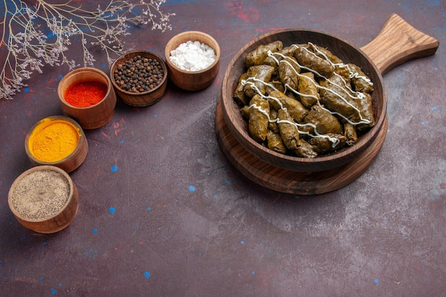 Vista superior delicioso prato de carne dolma com diferentes temperos em um fundo escuro.