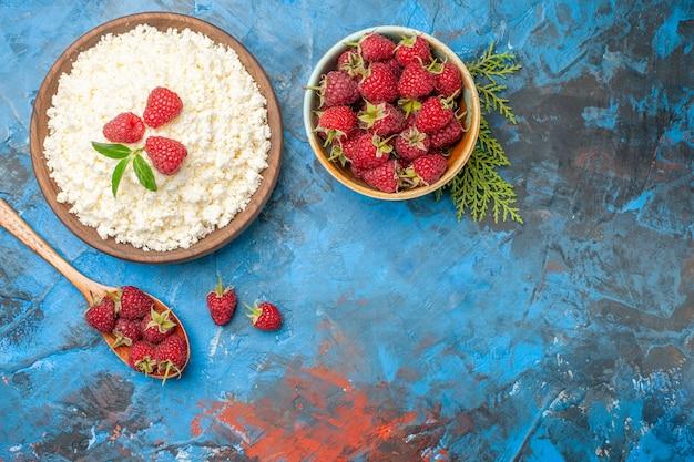 Vista superior delicioso queijo cottage com framboesas frescas em fundo azul.