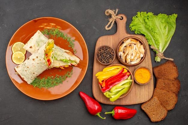 Vista superior - delicioso sanduíche de carne fatiada shaurma com pão escuro e vegetais em fundo escuro hambúrguer de sanduíche de salgadinhos