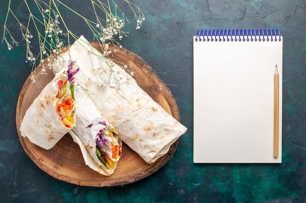 Vista superior delicioso sanduíche de carne feito de carne grelhada no espeto fatiada com o bloco de notas na mesa azul escuro.