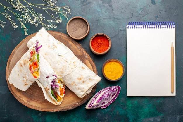Vista superior delicioso sanduíche de carne feito de carne grelhada no espeto fatiada com temperos e o bloco de notas na mesa azul.