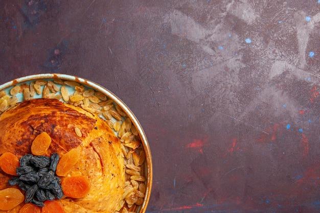 Vista superior - delicioso shakh plov cozido refeição de arroz com passas na mesa escura