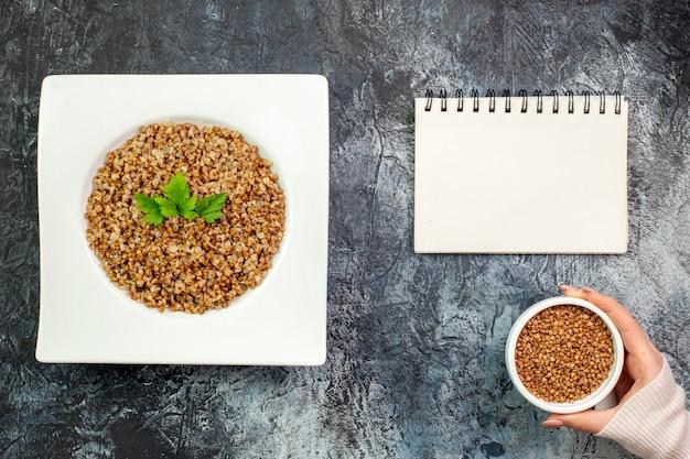 Vista superior delicioso trigo sarraceno cozido dentro do prato no fundo cinza claro refeição de calorias foto colorida prato comida de feijão
