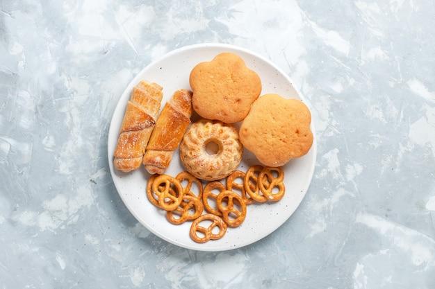 Vista superior deliciosos bagels com biscoitos e bolos dentro do prato na mesa branca clara.