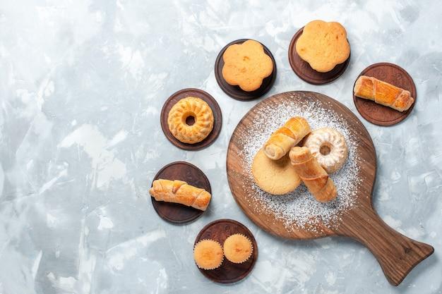 Vista superior deliciosos bagels com pequenos bolos e biscoitos sobre fundo branco claro.