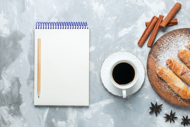 Vista superior deliciosos bagels com uma xícara de chá e canela, sobre fundo branco claro.