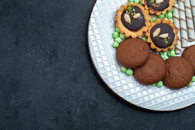 Vista superior deliciosos biscoitos com doces no fundo cinza biscoito açúcar assar bolo torta chá biscoito