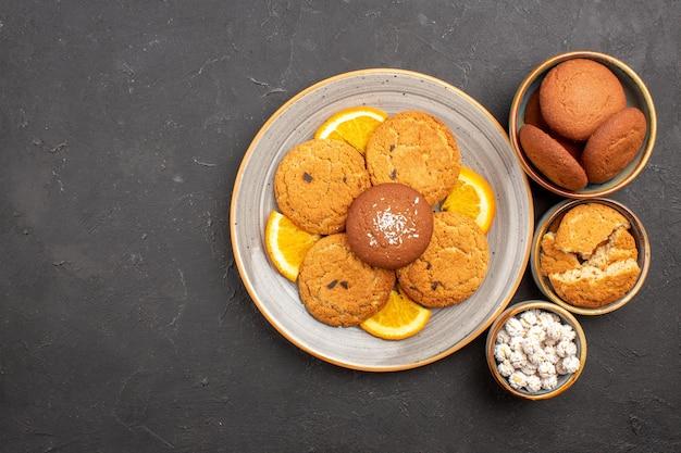 Vista superior deliciosos biscoitos com fatias de laranjas frescas em fundo escuro