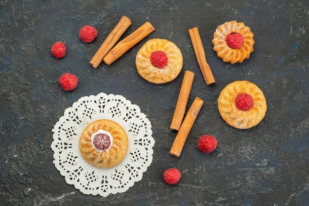 Vista superior deliciosos biscoitos com framboesas vermelhas frescas e canela na superfície escura.