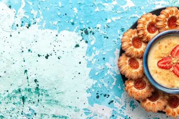 Vista superior deliciosos biscoitos com geléia e sobremesa de morango no fundo azul.