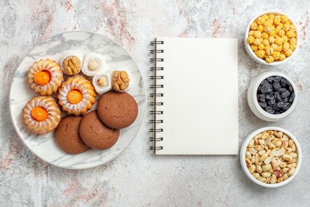 Vista superior deliciosos biscoitos com nozes e passas no fundo branco biscoito de nozes bolo doce açúcar