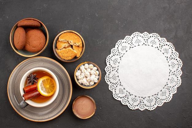 Vista superior deliciosos biscoitos com uma xícara de chá na superfície escura biscoito de açúcar sobremesa biscoito doce
