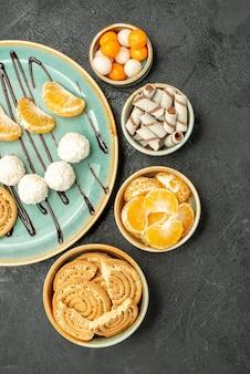 Vista superior deliciosos biscoitos de açúcar com doces em fundo cinza