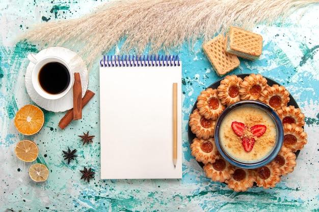 Vista superior deliciosos biscoitos de açúcar com waffles, xícara de café e sobremesa de morango na mesa azul