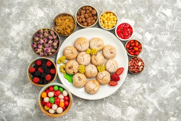 Vista superior deliciosos biscoitos de açúcar dentro do prato com diferentes nozes e doces no fundo branco biscoito de açúcar biscoito doce bolo chá